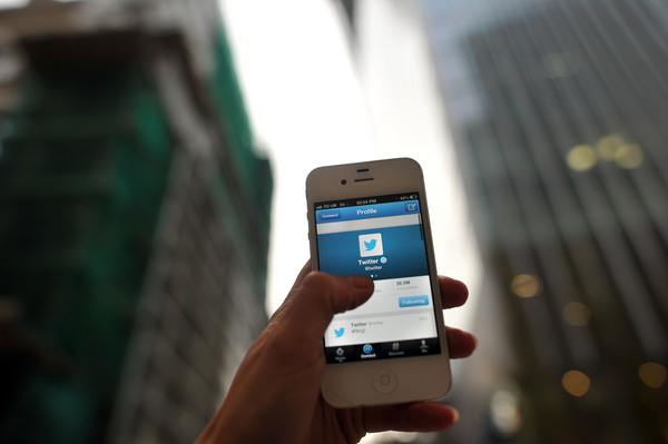 Man holding up iPhone displaying the Twitter App in a City with Sky Scrapers