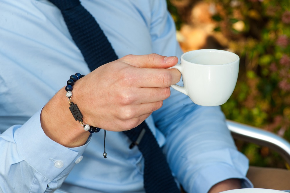 Man in smart suit wearing a bracelet drinking coffee