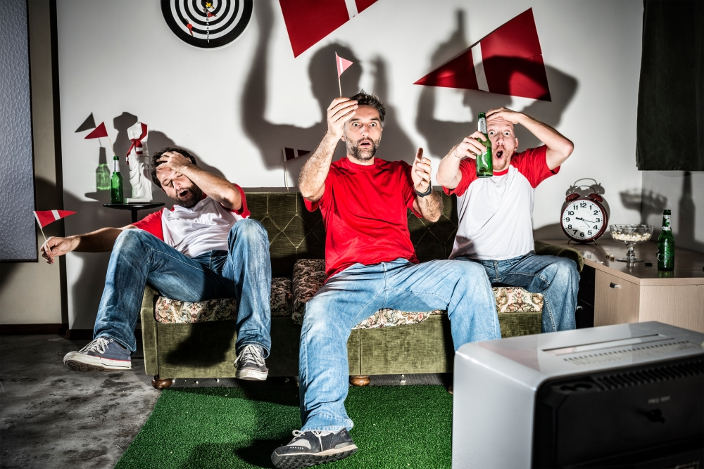 Three young adult men friends watching football: Missed goal disappointment
