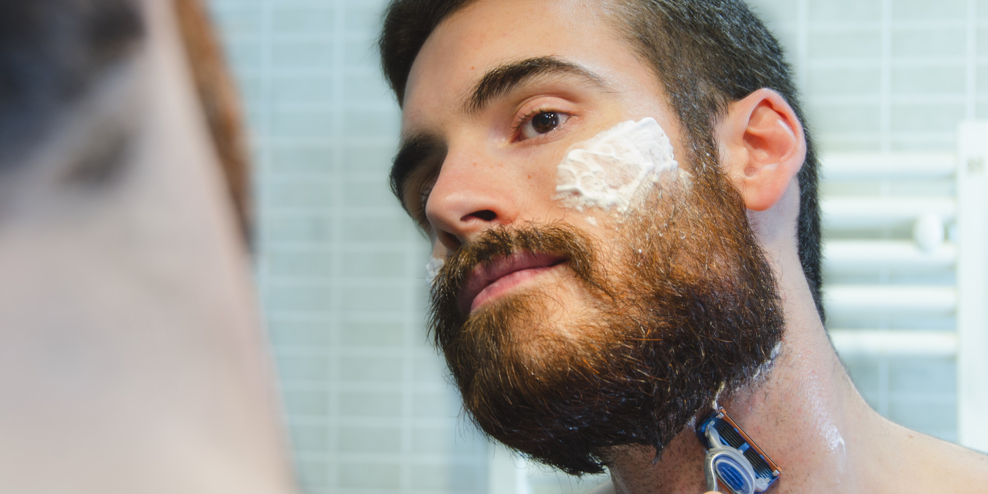 Man in the bathroom caring for his beard with a razor and shaving foam