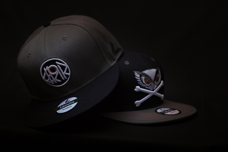 Two black snapback caps for men on a black background