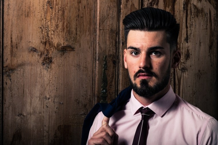 Very smart young man with blazer over his shoulder in front of wood background