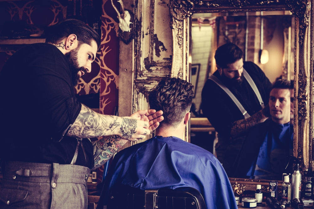 Young man in the barber's chair having his hair cut in front of a mirror