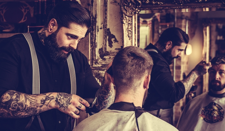 Man having hair cut in the barbers chair by barber man who has tattoos