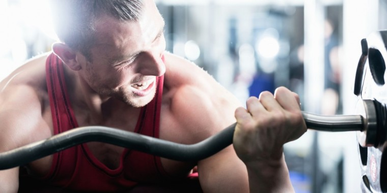 Man in gym lifting weights ahead of getting fit