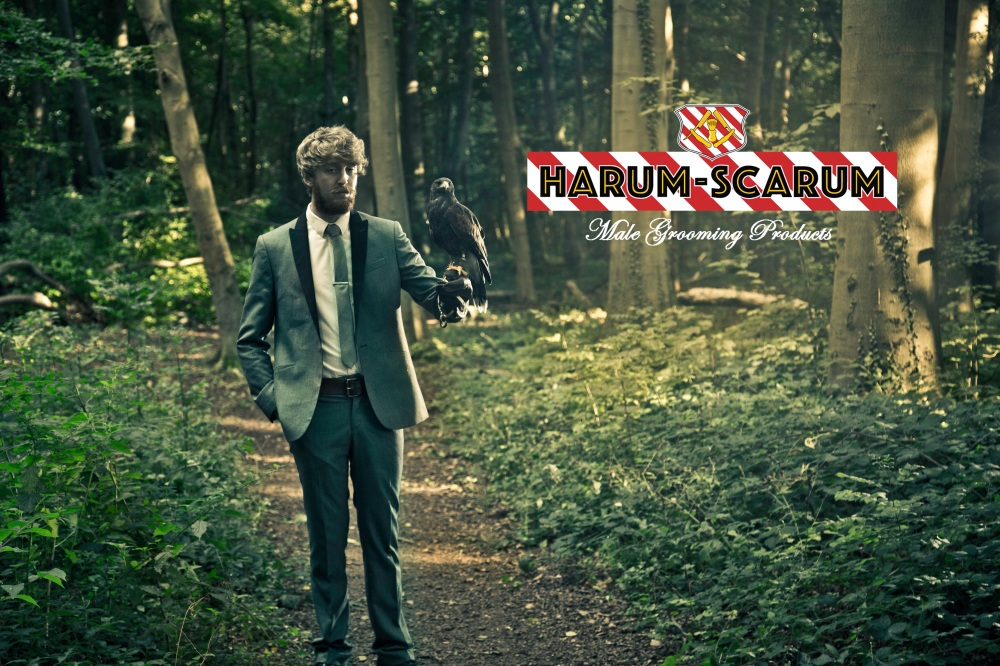 Man stood in forest in a suit with a bird of prey on his arm