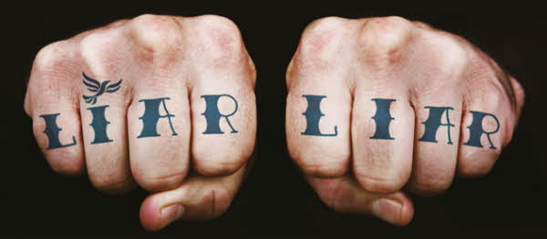Man's hands with Liar Liar tattoo across knuckles with fist clench