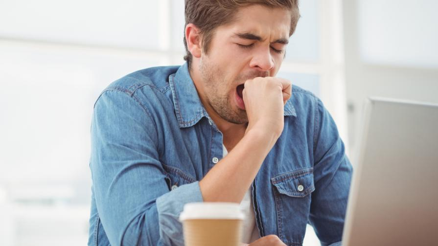 Young man yawning in front of computer screen with a coffee.