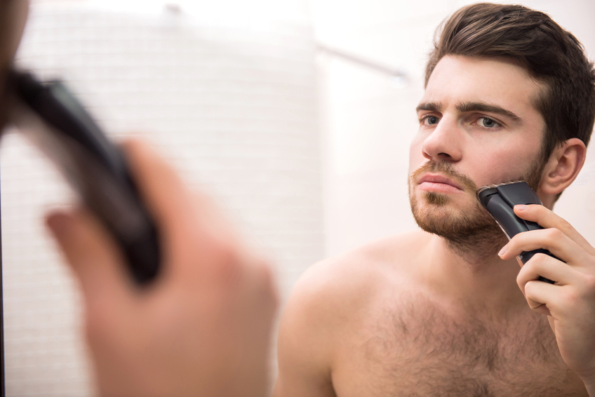 Man shaving face in the mirror with electric razor