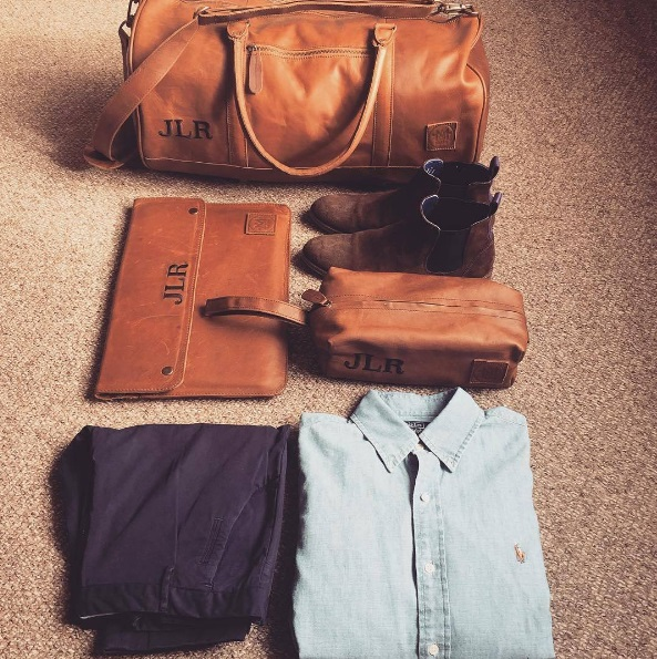 Clothes fodled with leather bag for weekend away