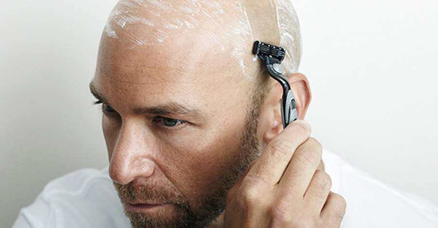 Man shaving head going bald in the mirror