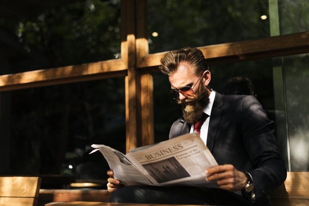 Should You Shave Your Beard for an Interview, smartly dressed man with beard reading a newspaper, bearded man, bearded in in sunglasses, man reading the newspaper, beards for business