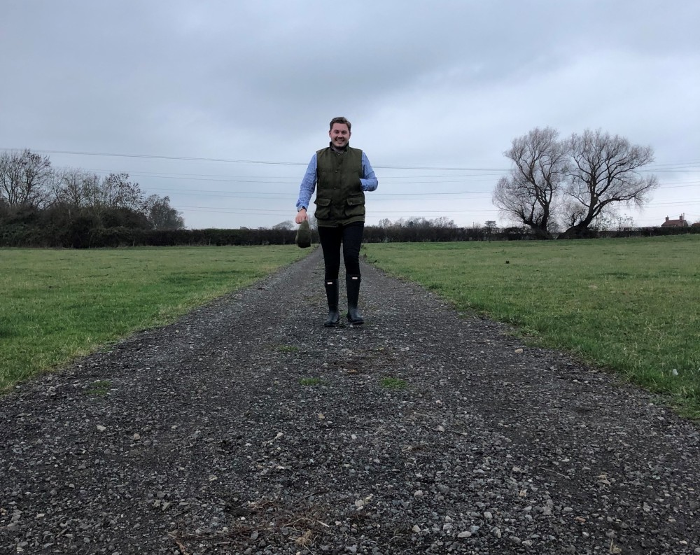 Man wearing gilet and wellies walking through a field on a grey day in the countryside.